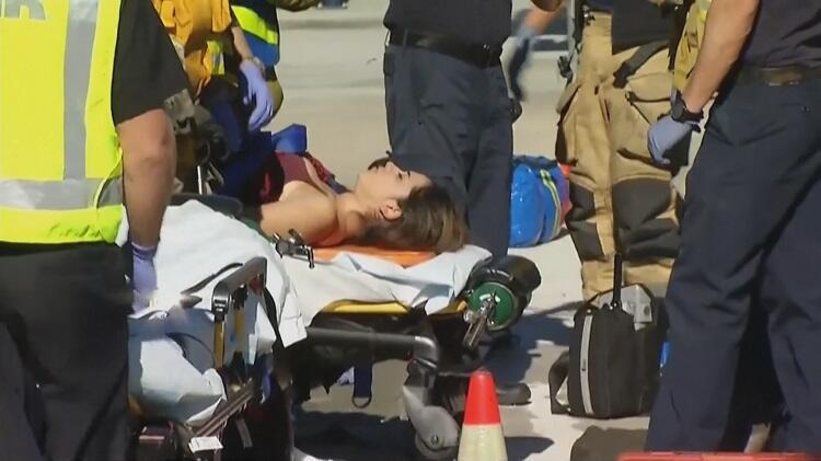 Una joven es trasladada en camilla en la zona del tiroteo