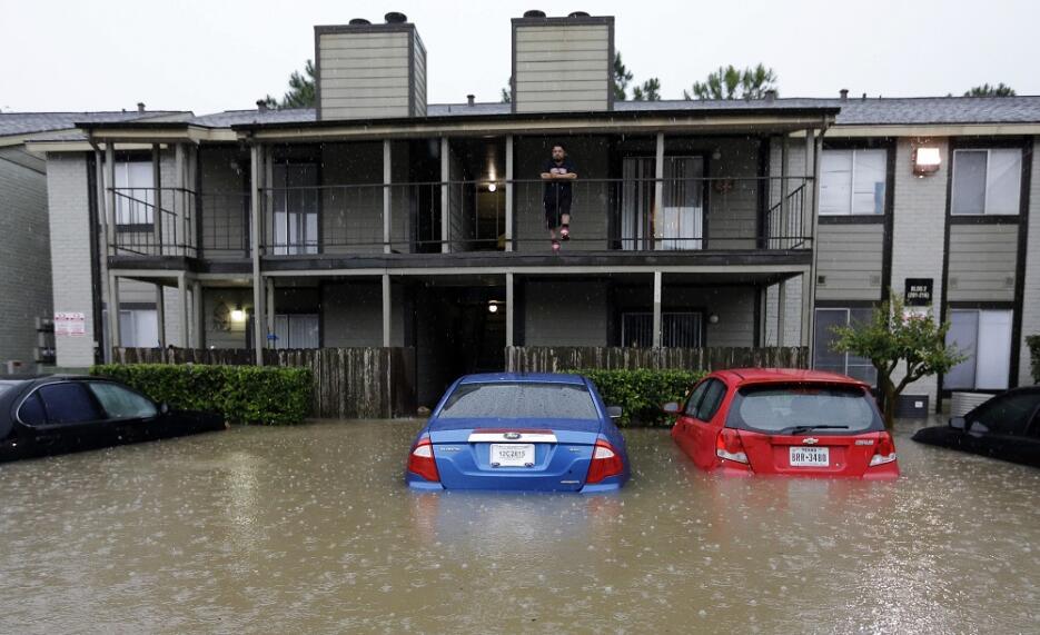 Un residente de Houston mira desde el segundo piso el parqueo inundado d...