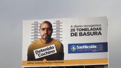 """Vista de una valla con la imagen de un ciudadano y el rótulo: """"Detenido..."""
