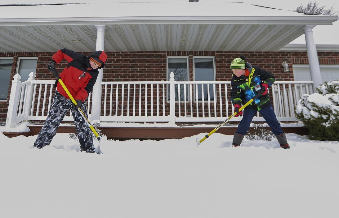 Dos chicos palean nieve frente a su casa en Iowa