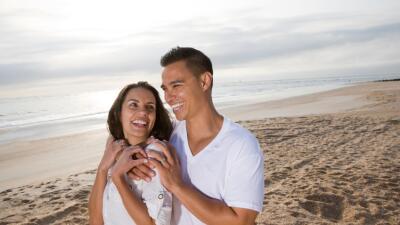 Pareja de enamorados pasea por la playa