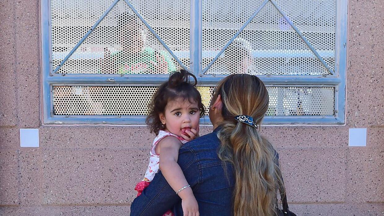 Una mujer con su hija en Nogales, Arizona, hablando con personas del otr...