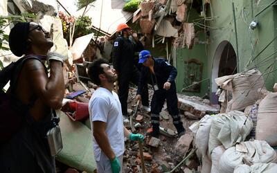 Voluntarios ayudan a remover escombros de un edificio que colapsó...