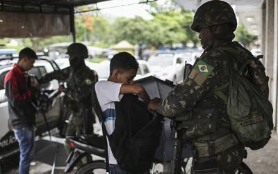 La imagen de policías militares revisando las mochilas de ni&ntil...
