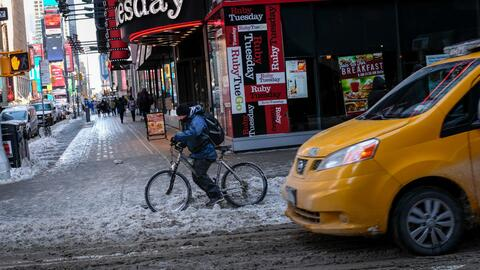 Un ciclista pasa por Times Square en medio del ciclón bomba que a...