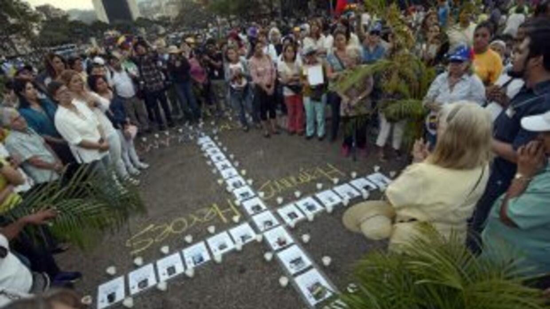 Los manifestantes protestan con una cruz formada con los retratos de las...