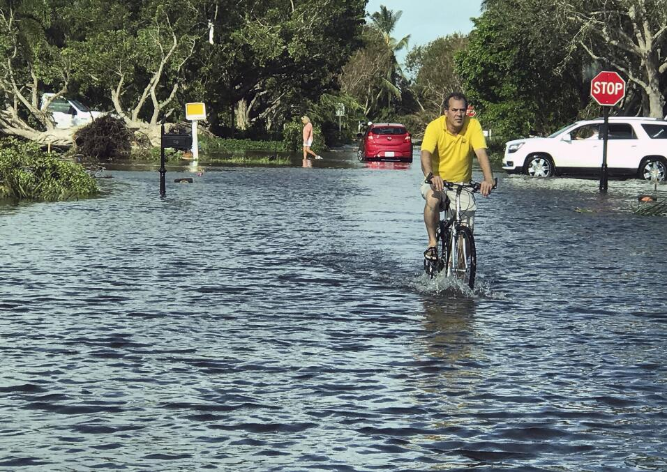 A man rides through storm water in Naples, Fla., in the aftermath of Hur...