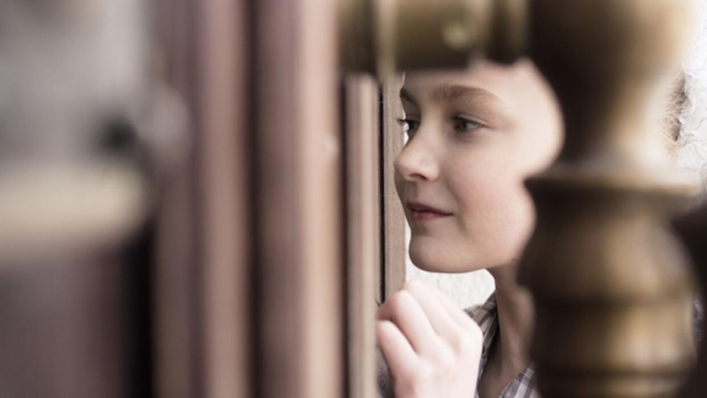Niño hablando con desconocido a través de la puerta