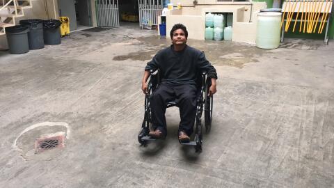 Un hombre en silla de ruedas descansa en el patio de la Casa del Migrant...