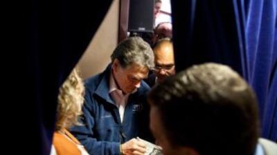 Rick Perry firma autógrafos antes del anuncio de los resultados en Iowa.