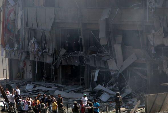 Lebanese citizens stand in front of a severely damaged building as they...