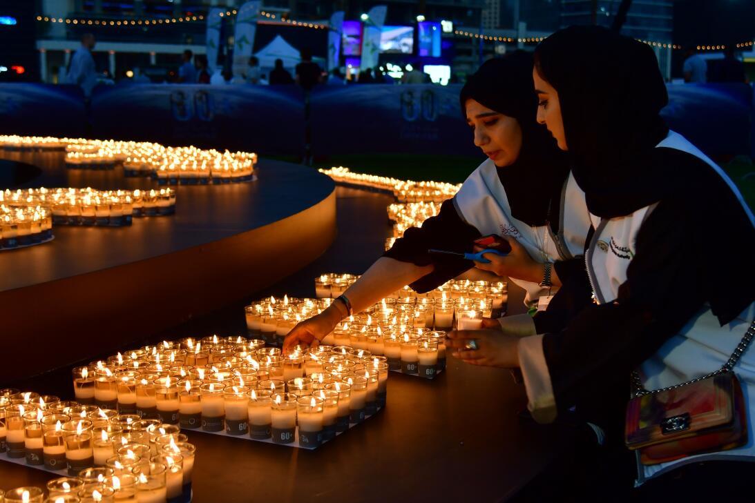 Dos mujeres encienden velas después de que se apagaran las luces de los...