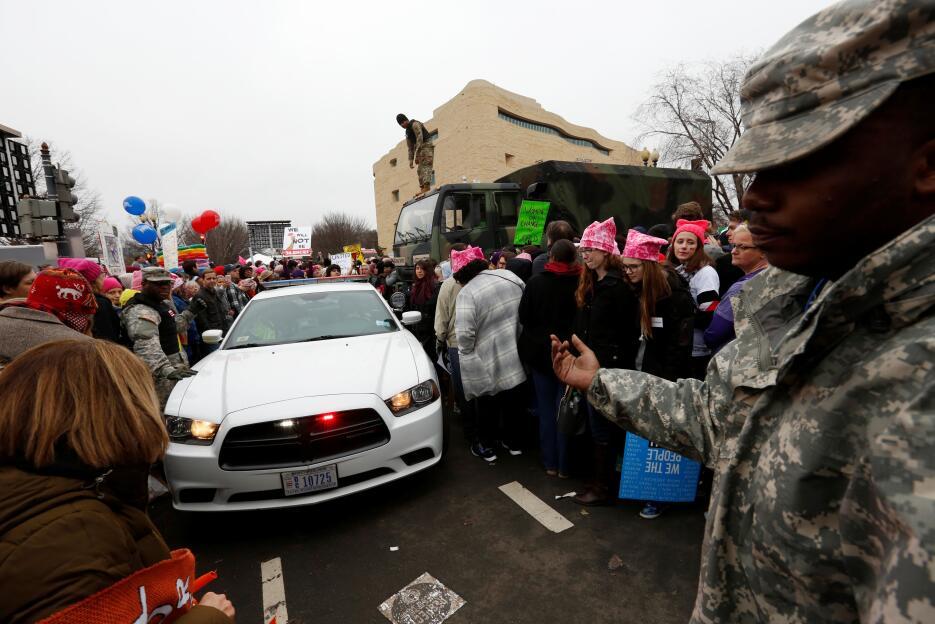 Un coche de policía trata de avanzar a través de la Marcha de la Mujer e...