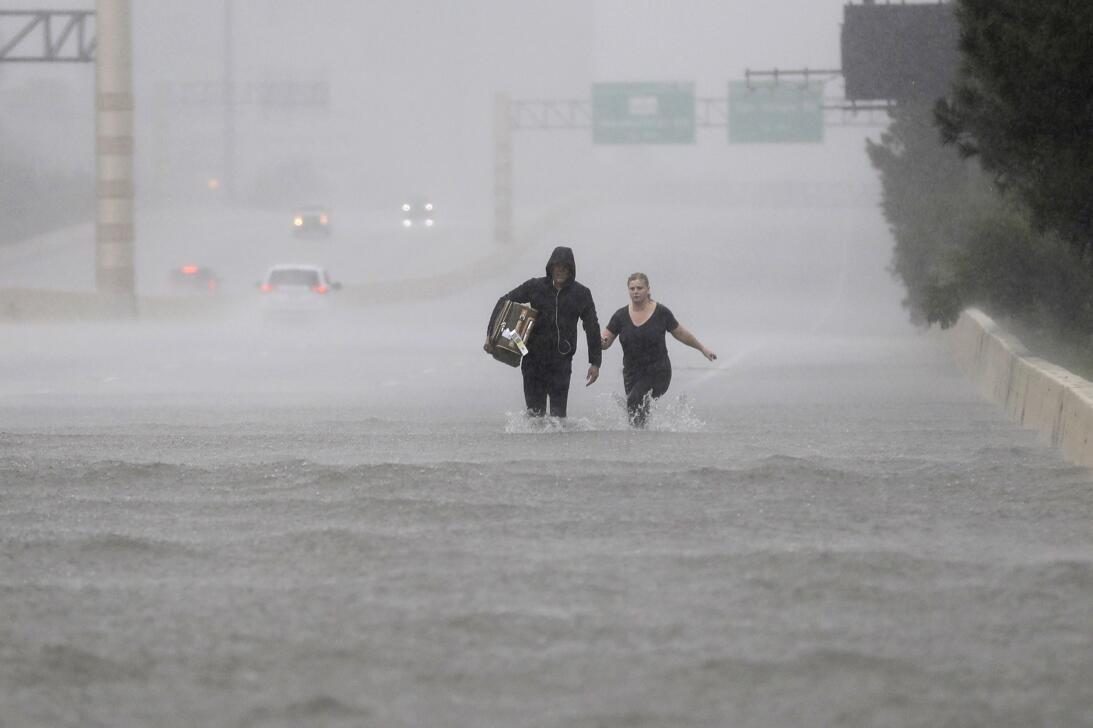 Dos personas caminan por una sección inundada de la Interstatal 610.