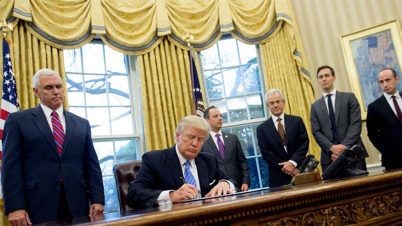 Stephen Miller (en la derecha) en el Despacho Oval mientras Trump firma...