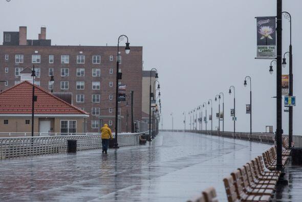 Un hombre camina por el paseo marítimo, mientras se observa el clima llu...