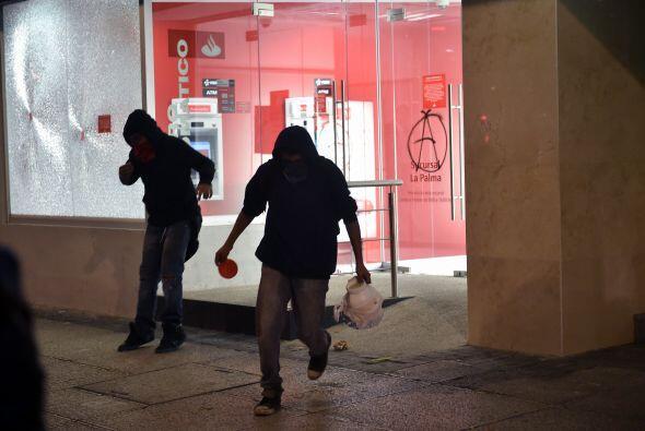Encapuchados realizan destrozos en un banco luego de la marcha por Ayotz...