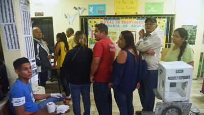 Un grupo de votantes hace fila en un centro electoral de Tegucigalpa, ca...