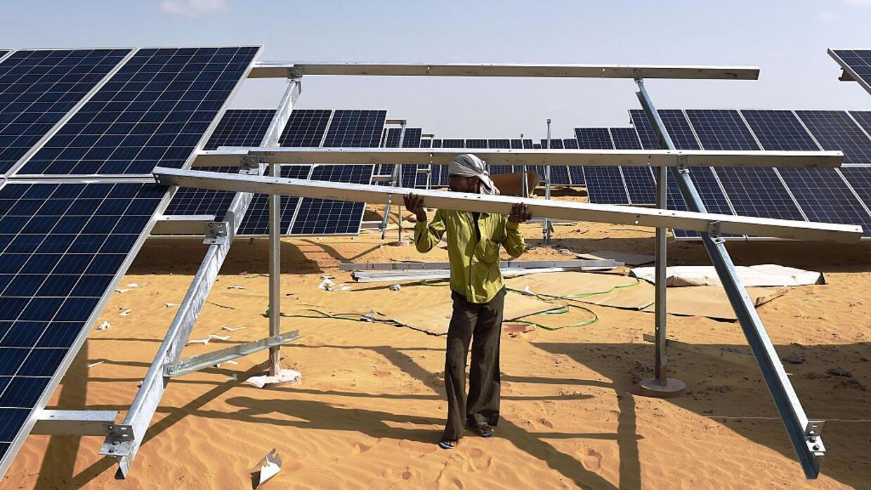 Un ingeniero indio arregla uno de los paneles solares de la planta ubica...