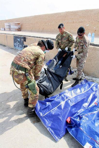Varios hombres trasladan los cuerpos de tres de los 94 inmigrantes muert...