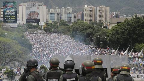 Bolivarian National Guards stand on a highway overlooking an anti-govern...