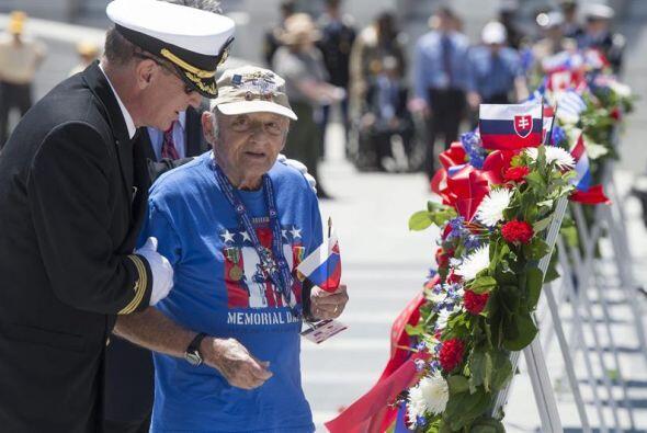 El veterano de la Segunda Guerra Mundial Donald Marks coloca unas flores...
