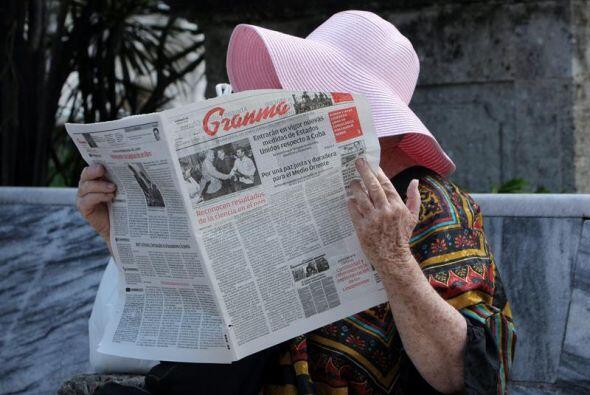 Una mujer lee el periódico Granma, que abre información de...