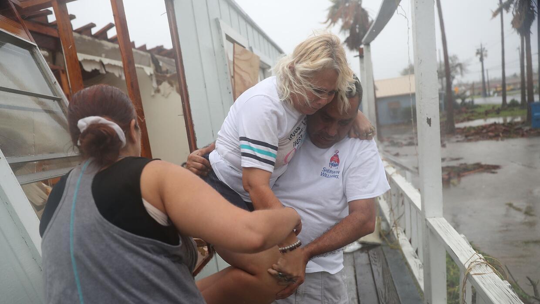 La residente de Rockport, Donna Raney es asistida para salir de su casa,...