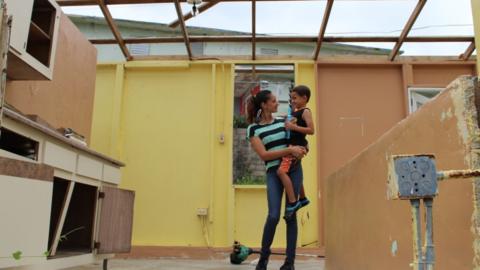 Jennifer Rodríguez y uno de sus dos hijos, residentes del barrio...