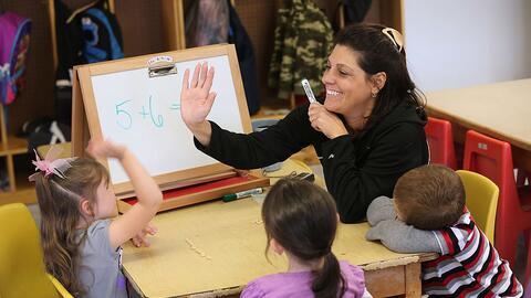 Teacher Denise Severing congratulates a child during a math lesson at th...