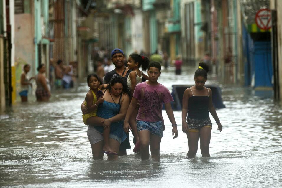 Las personas deben caminar por el agua, en las calles de inundadas de La...