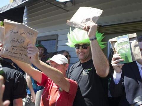 """Compradores celebran afuera de la tienda de marihuana """"Cannabis Cit..."""