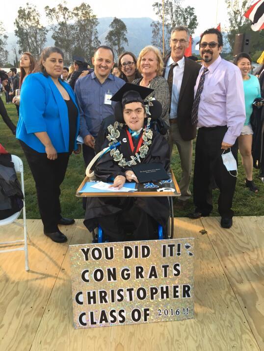 Christopher León en el día de su graduación con sus padres y educadores