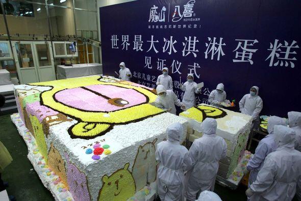 Trabajadores chinos de la ciudad de Beijing preparar un pastel de helado...