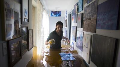 Matthew Koser busca doumentos dentro de la casa de sus abuelos en Bear C...