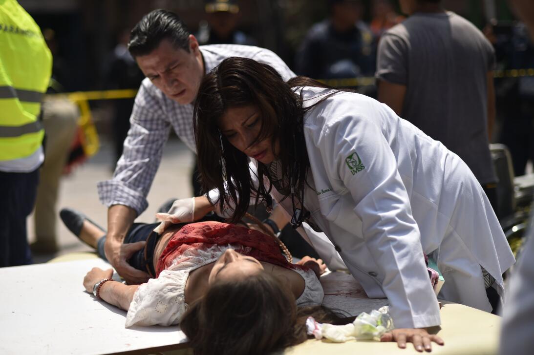 Una mujer herida durante el sismo es asistida por paramédicos en la ciud...