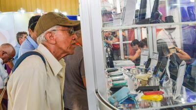 Un asistente a la Feria Internacional de La Habana mira ofertas de móviles.