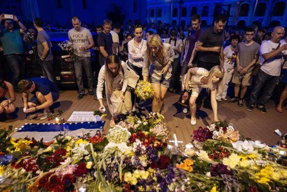 Personas dejan ramos de flores en conmemoración de las víctimas del avió...