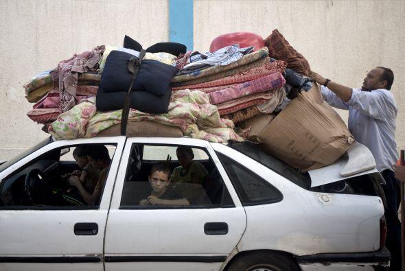 Un gazatí amarra sus pertenencias al techo de su coche ya que él y su fa...