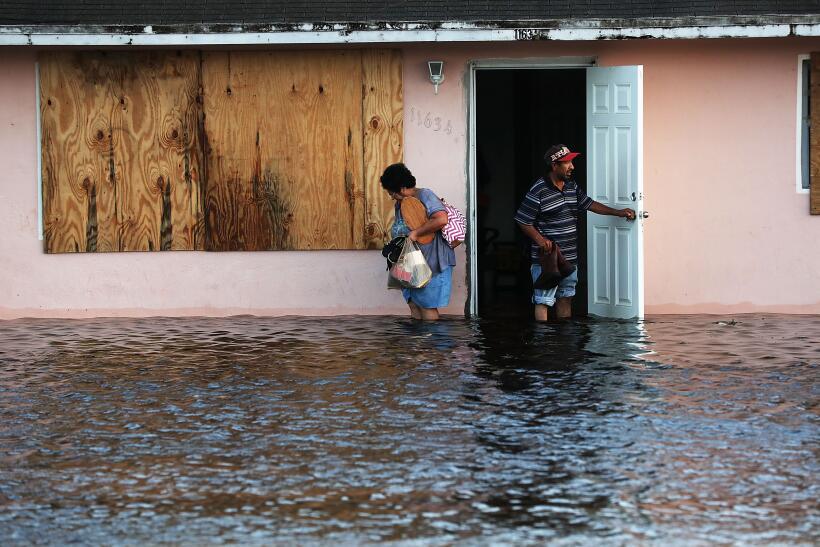 Una pareja deja su hogar inundado en la mañana de este lunes en los alre...
