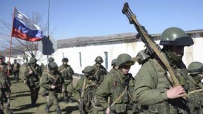 Un hombre con una bandera de Rusia saluda a los hombres armados en unifo...