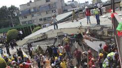 Los trabajadores de rescate buscan personas atrapadas en los escombros d...