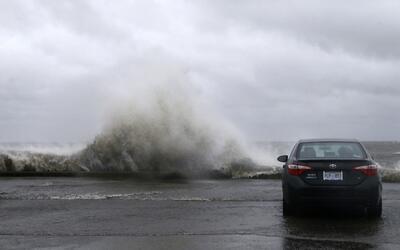 Varias personas observan, sentadas en el interior de un coche, las olas...
