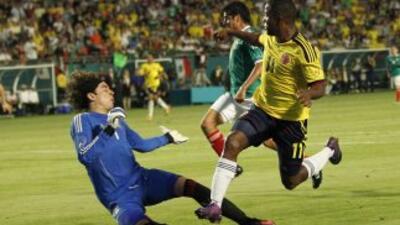 Dorlan Pabón y Memo Ochoa en un mano a mano ganado en esta jugada por el...