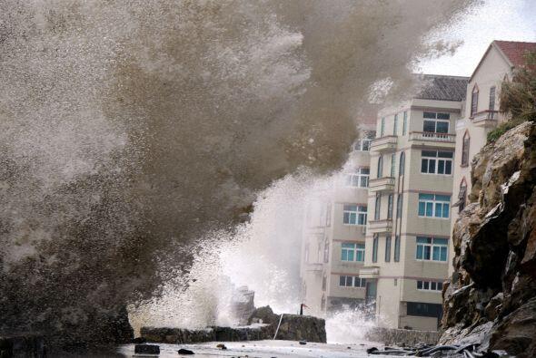 Las grandes olas llegan a un camino después de tifón Fitow tocó tierra e...