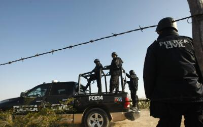 Policías mexicanos reguardan el lugar del crimen contra una perso...