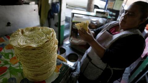 Una mujer arregla una pila de tortillas de maíz recién hec...