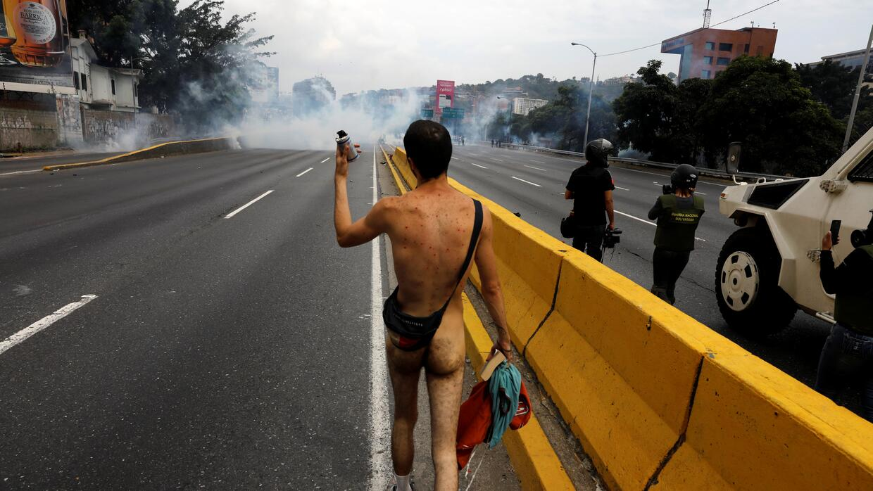 In photos: the Venezuelan demonstrators who jumped into a stinking river...