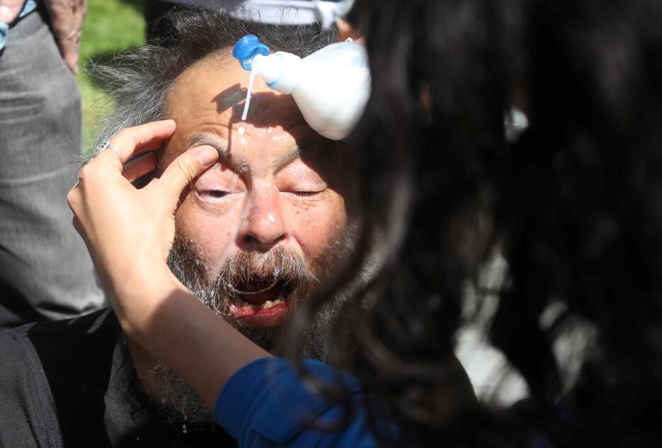 Un anciano es atendido luego que le rociaran gas pimienta en el rostro.