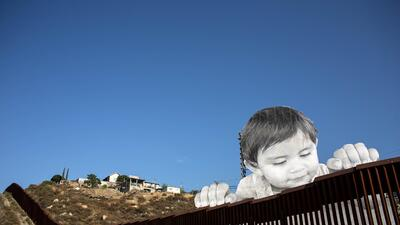 What is this curious child thinking as he peers over the border wall?